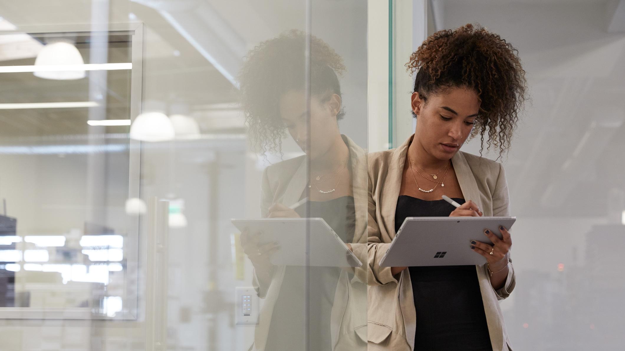 Žena si zapisuje poznámky na tabletu Surface vpráci.