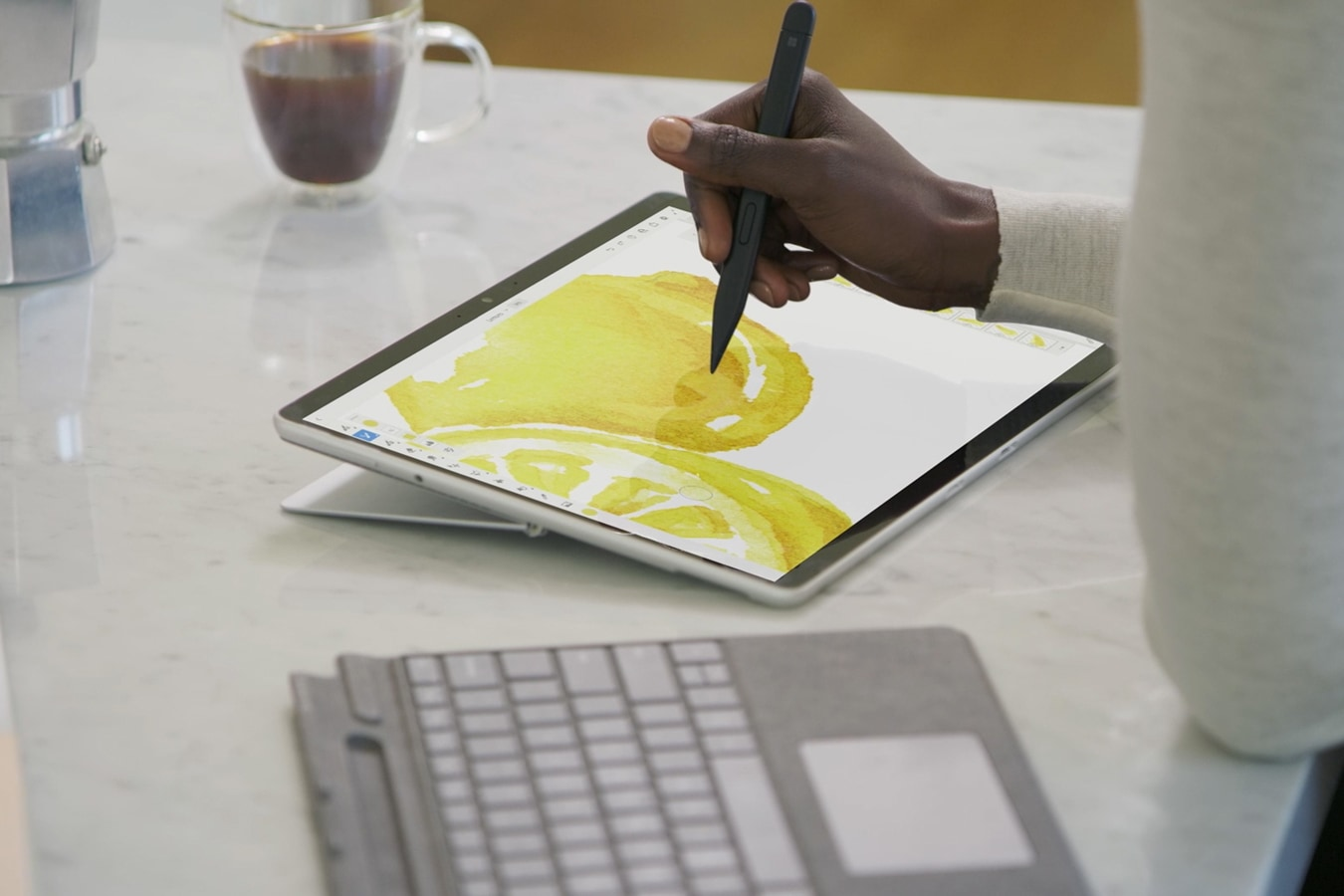 A person drawing with a Surface Slim Pen 2 on a detached Surface Pro 8.