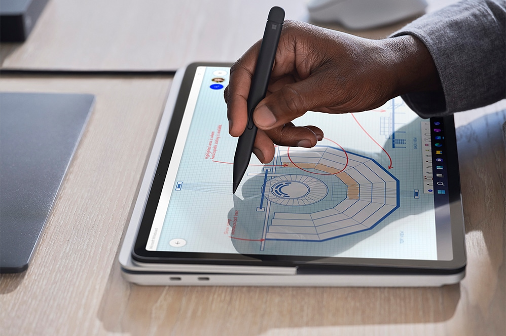 A close-up view of a person's hand using Surface Slim Pen 2 to sketch on Surface Laptop Studio in Studio Mode
