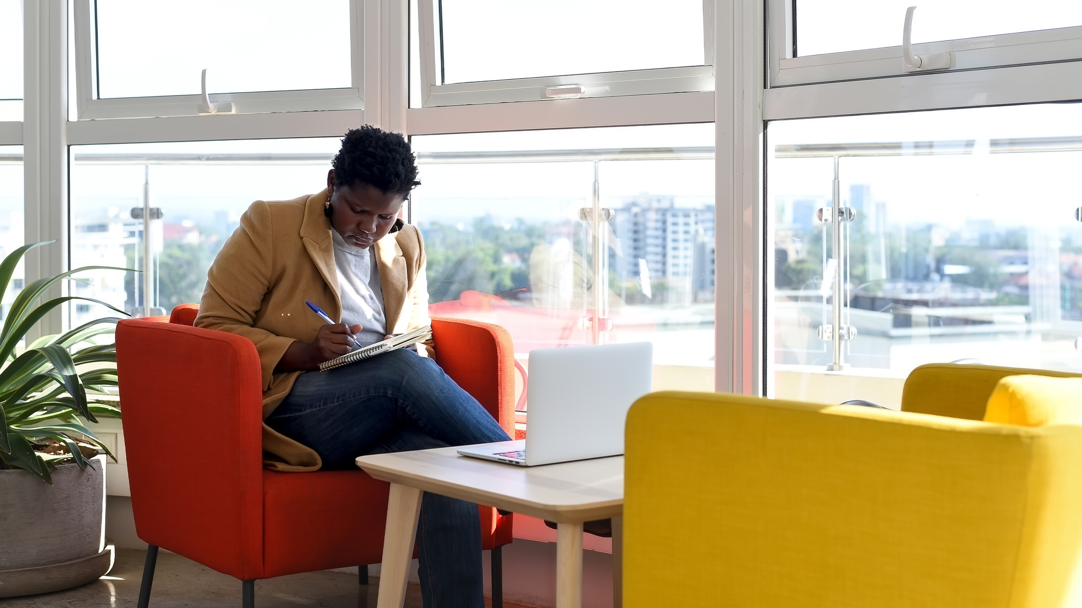 A woman takes notes while sitting with her laptop in a modern office.