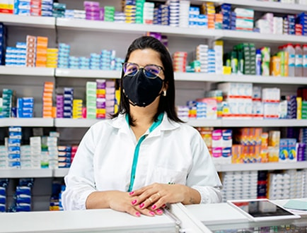 A pharmacist wearing a mask standing in front of a wall of medications.