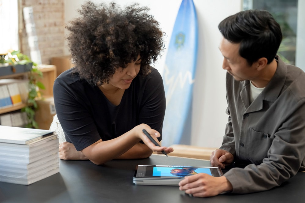 A pair of workers collaborate over Surface Laptop Studio in studio mode.