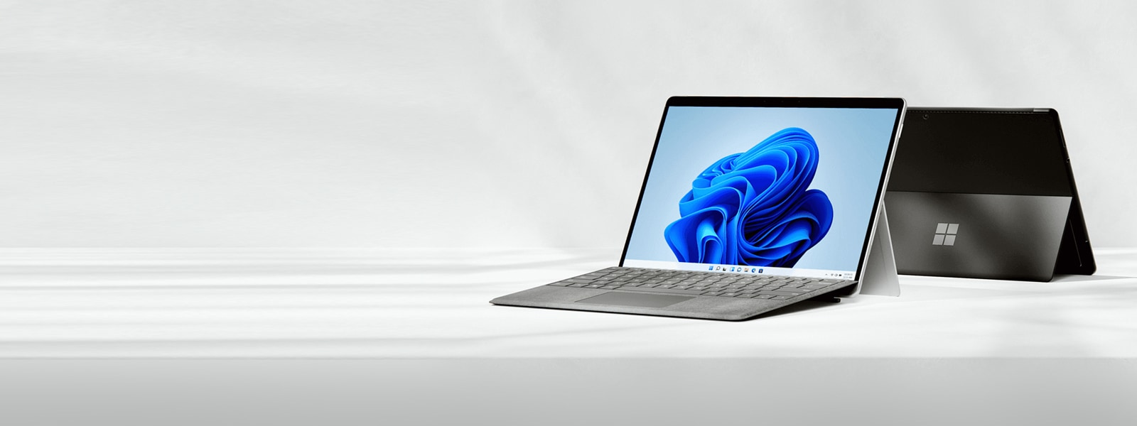 Two Surface Pro 8 devices in kickstand mode.