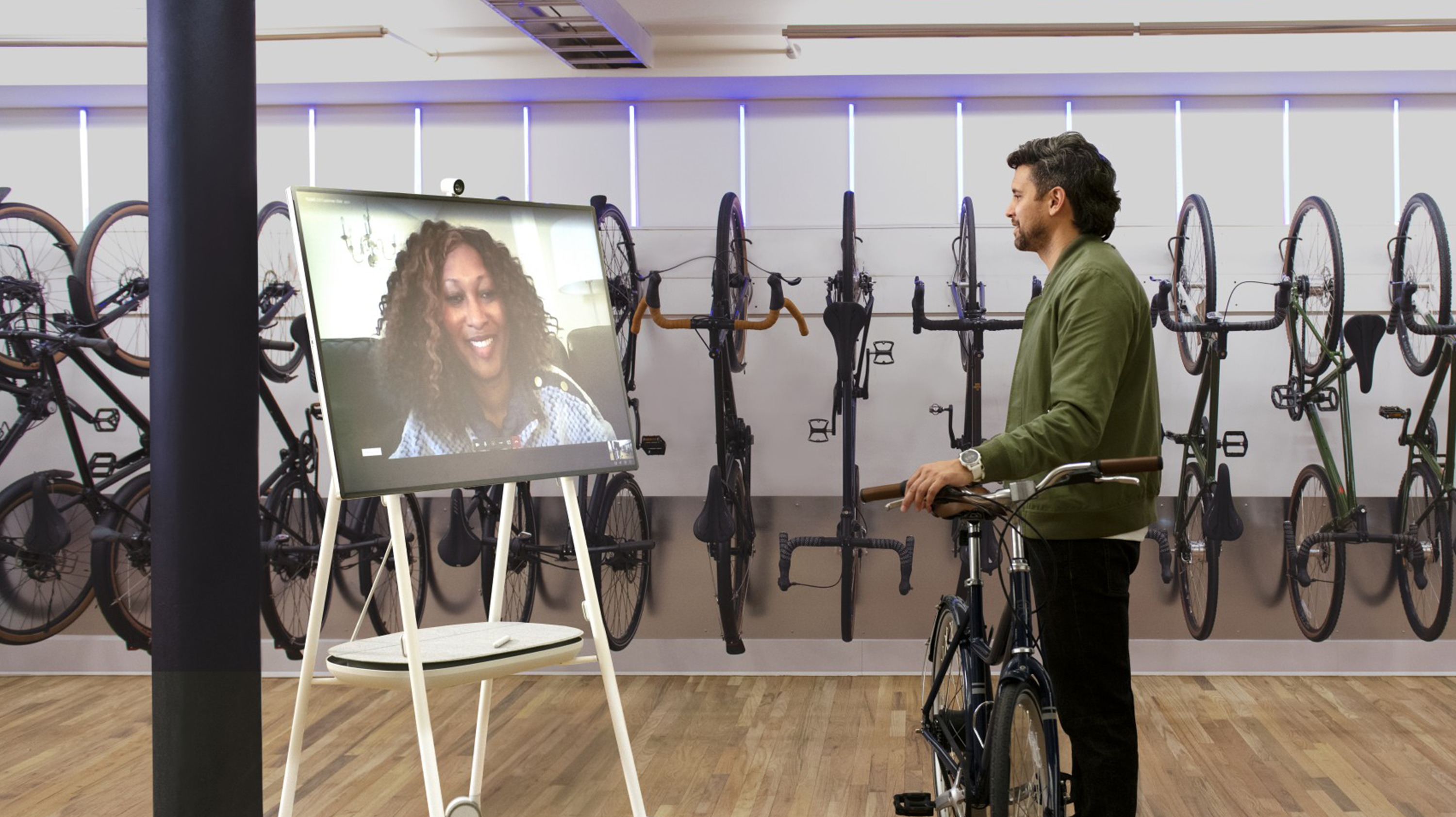 A man in a bicycle shop has a conversation with a woman on a Surface Hub.