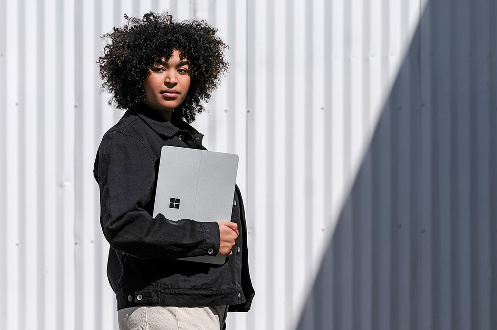 A person stands outside with Surface Laptop Studio.