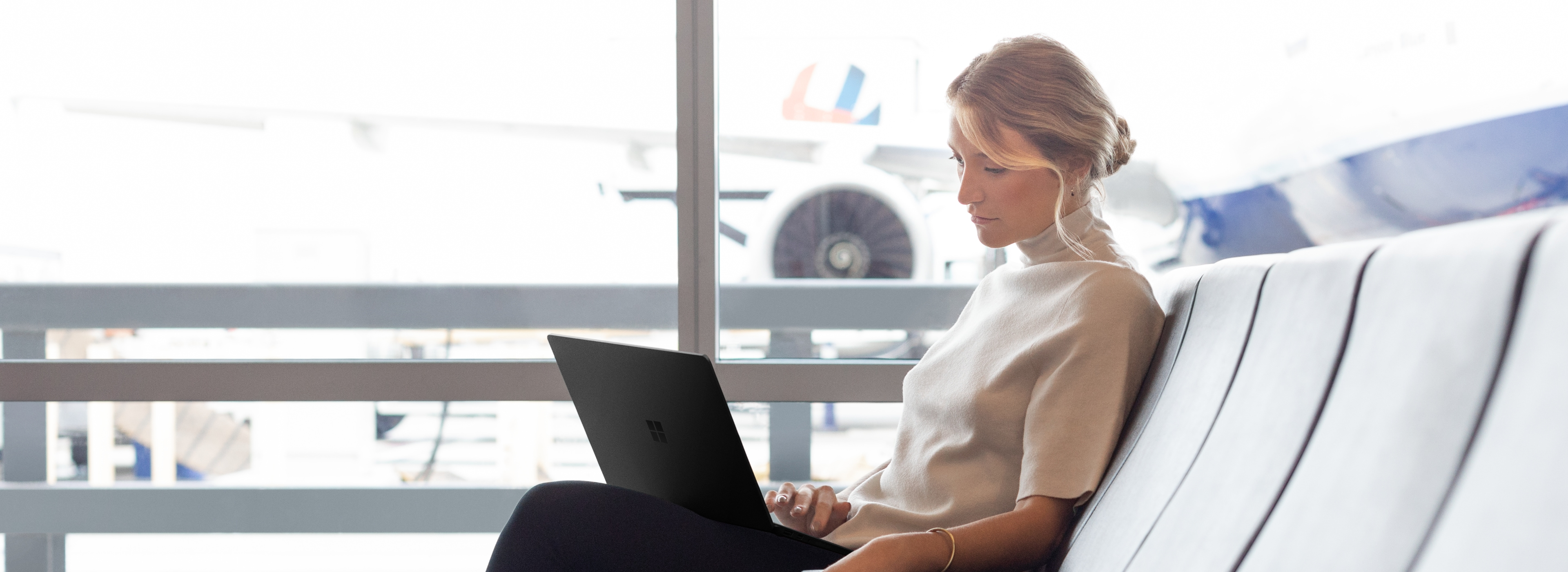 A person sitting in an airport using a laptop.