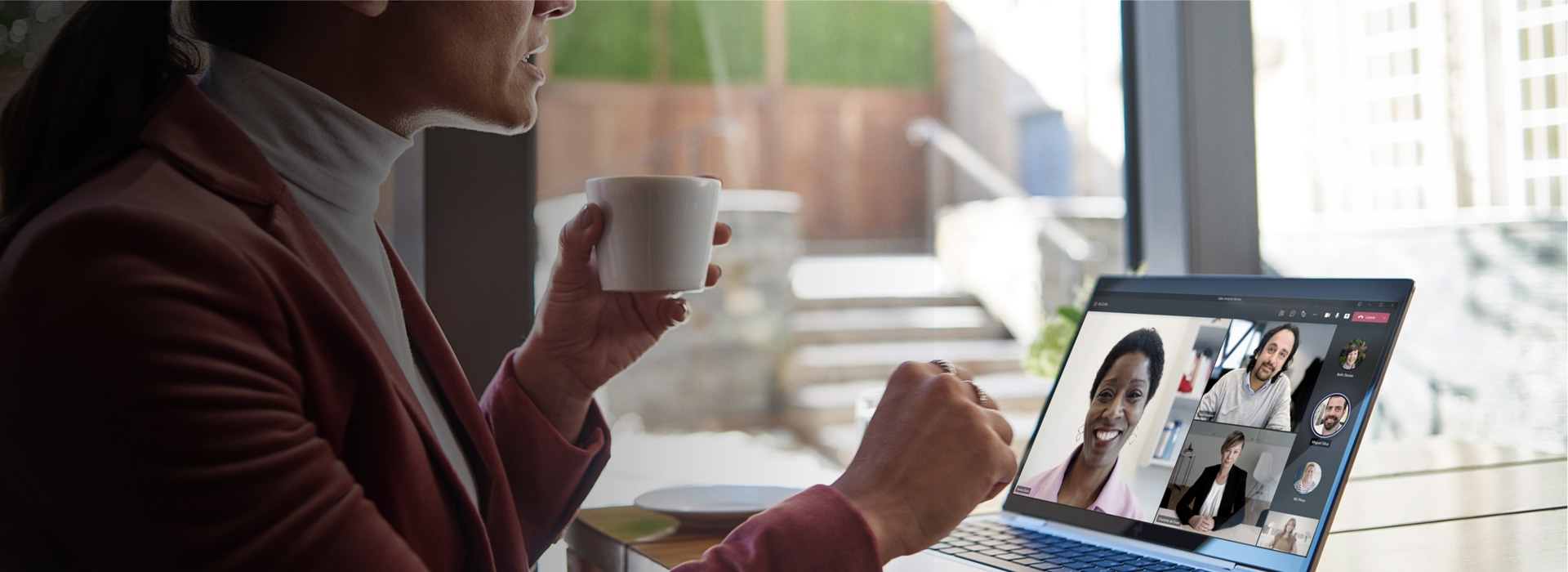 A person holding a coffee cup while on a Teams video call on a laptop.