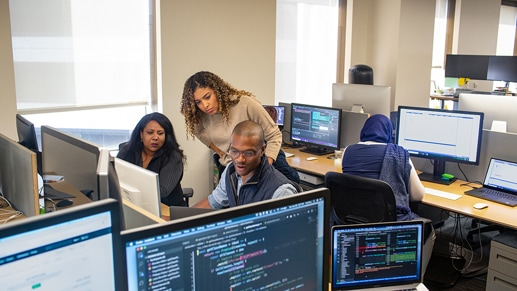 Three people in an office looking at a computer screen.
