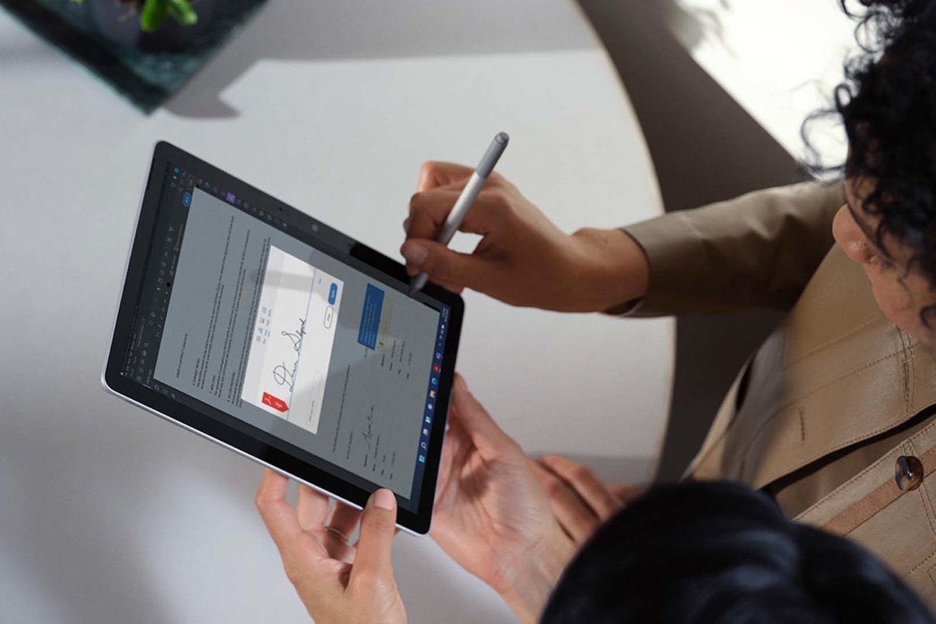 Ylhäältä otettu kuva kahdesta työtoverista, jotka tarkastelevat yhdessä asiakirjaa Surface Go 3 -laitteella