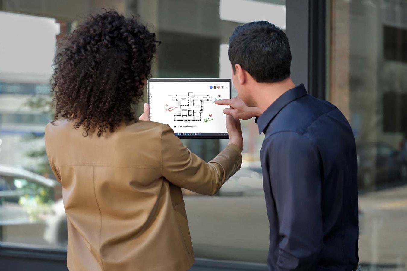 兩個人站在店面外,使用採用平板電腦模式的 Surface Pro X 拍照