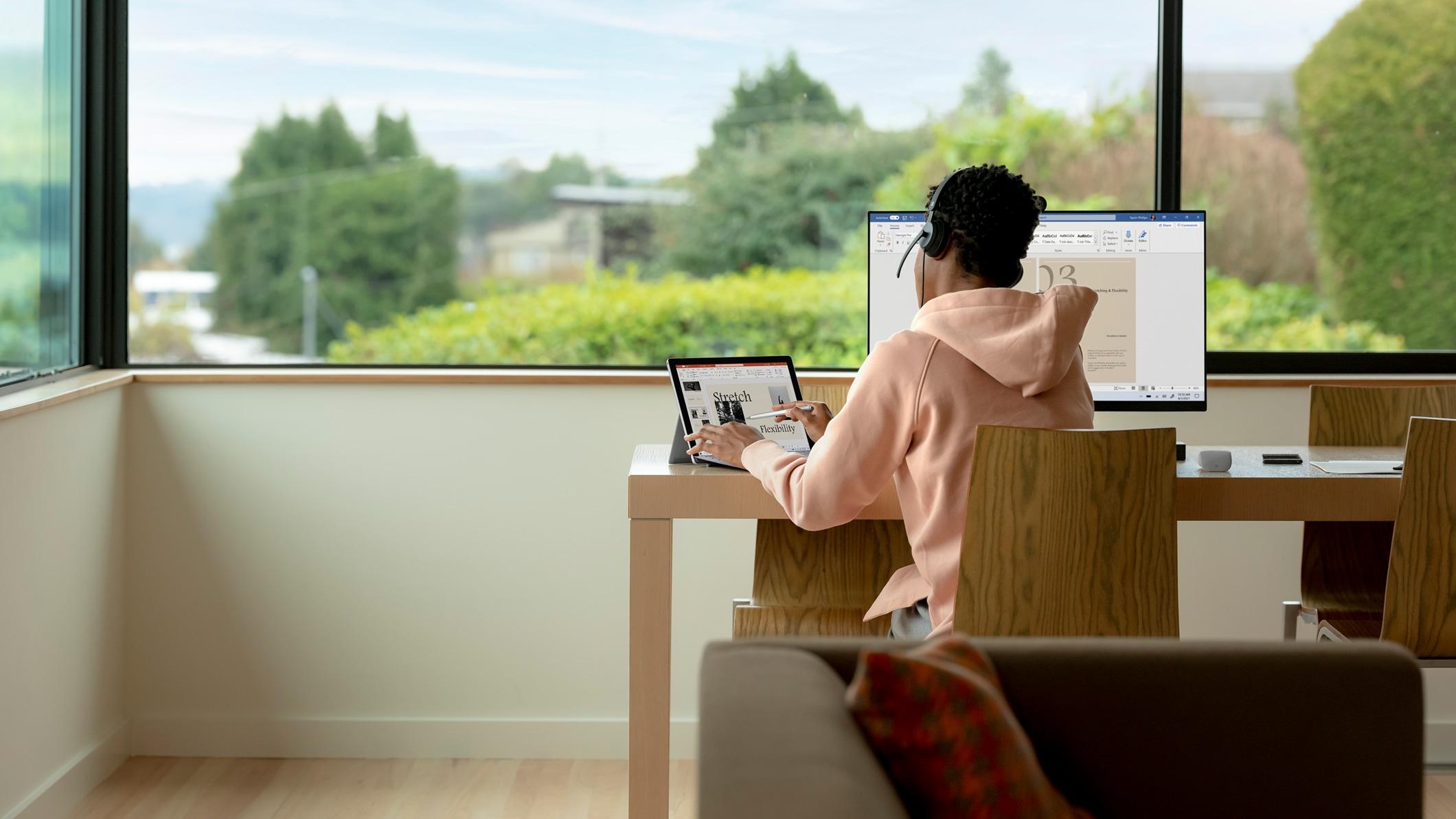 Egy diák íróasztalnál ülve Office-alkalmazásokat használ laptopon és monitoron.