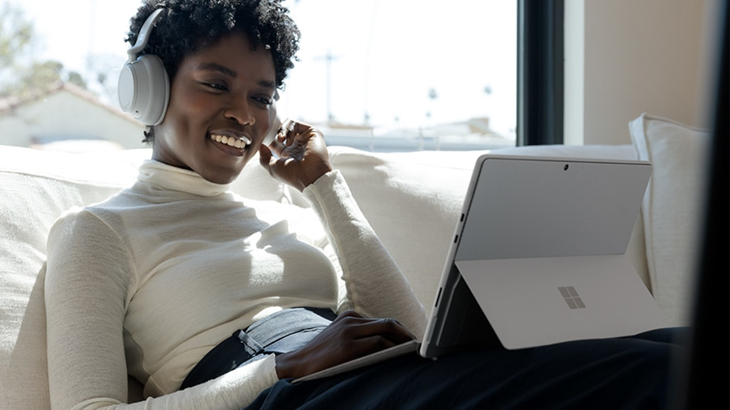 A person uses Surface Headphones and Surface Pro 8 to connect.