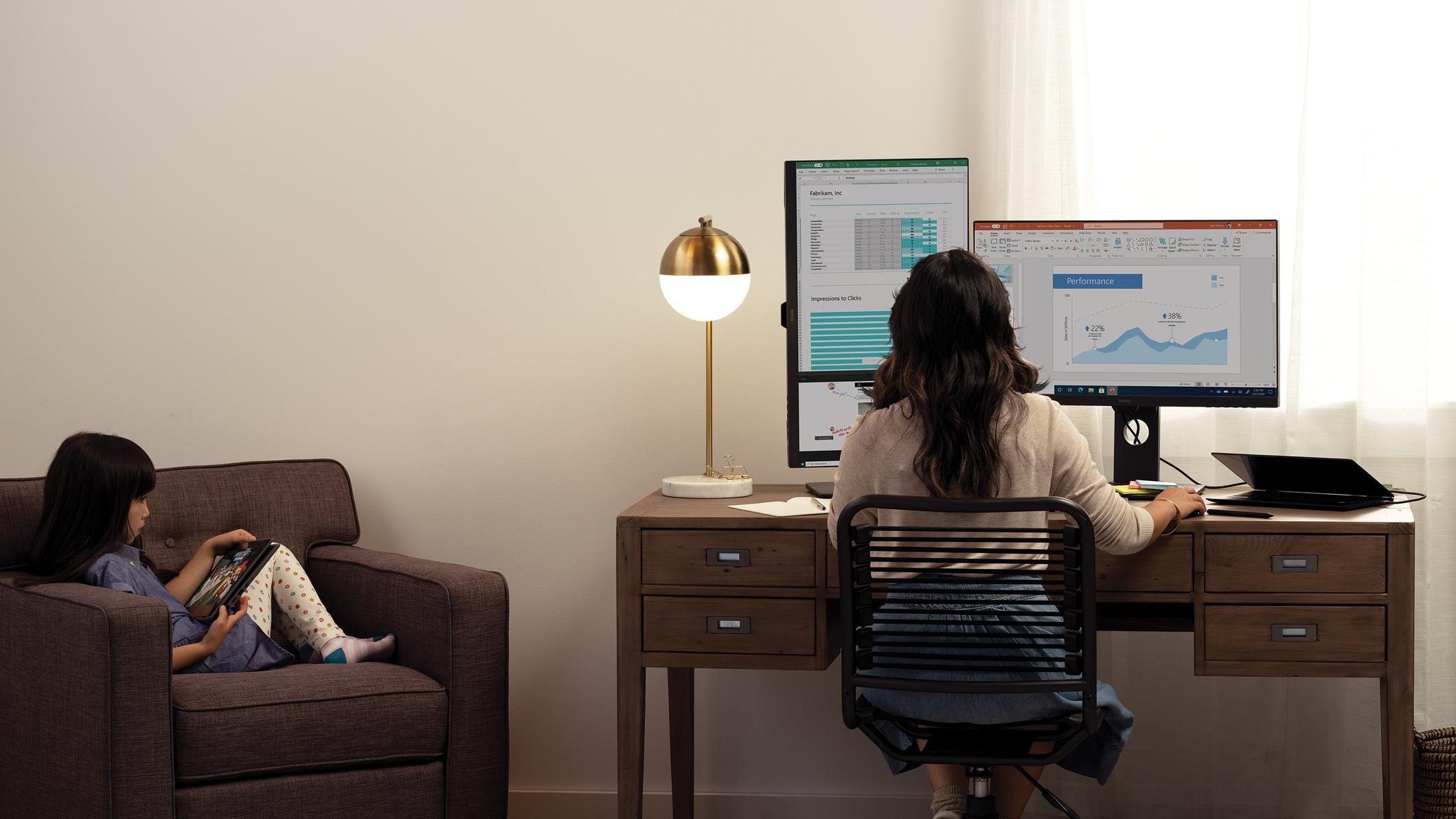 コンピューターで Office アプリを使いながら、自宅で子どもと過ごしつつ働く女性。