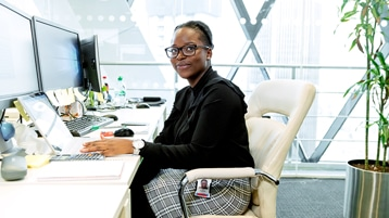 A smiling person sitting at their desk with multiple screens.