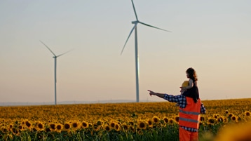 A worker with a child riding on their shoulders standing in a field of sunflowers with wind turbines in the distance.