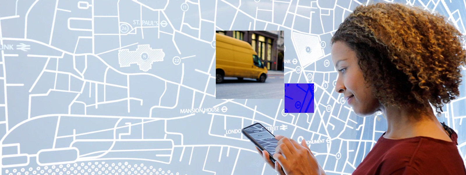 Woman uses a mobile device in front of a map display with an abstract overlay