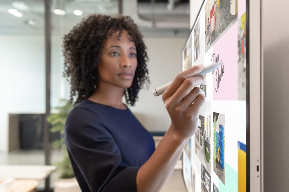 An executive working on Surface Hub 2S with Surface Hub 2 Pen.