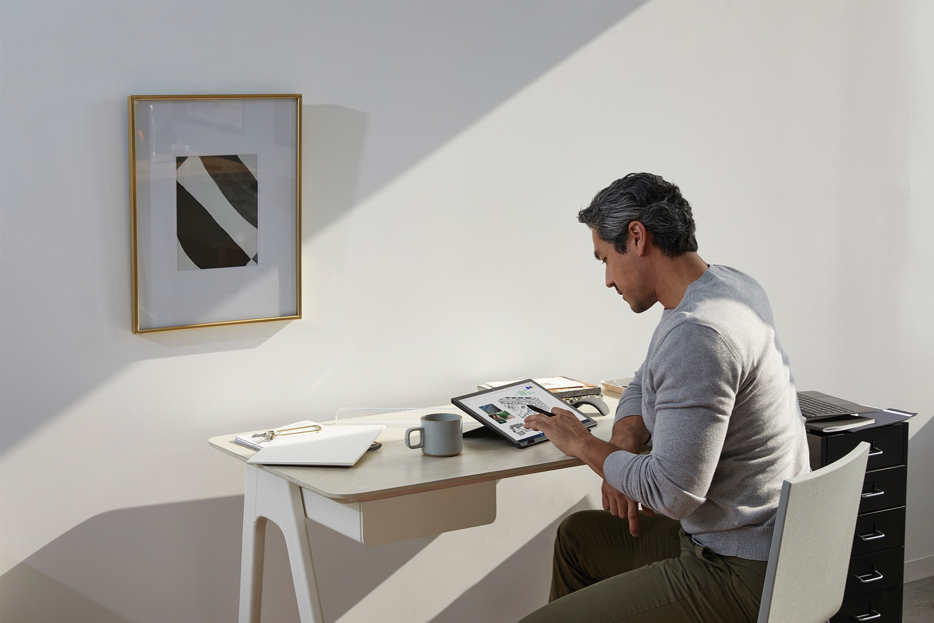 A person working from home works with Surface Pen on his Surface Pro
