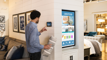 A person using a digital screen on a wall inside of a furniture store.