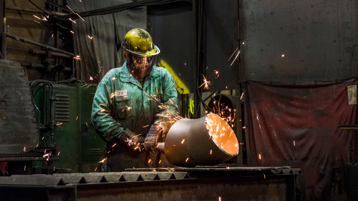 Sparks flying around a welder who is working on a metal tube.