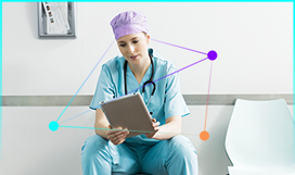 A medical professional in scrubs with a stethoscope around their neck looking at a tablet.