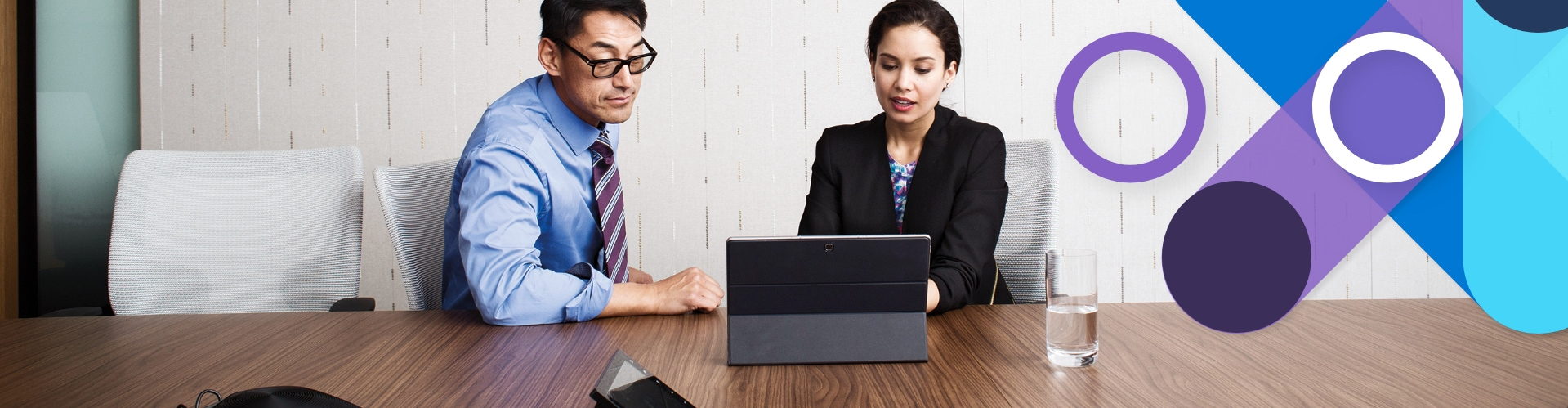Two professionals sitting at a table looking at a laptop.