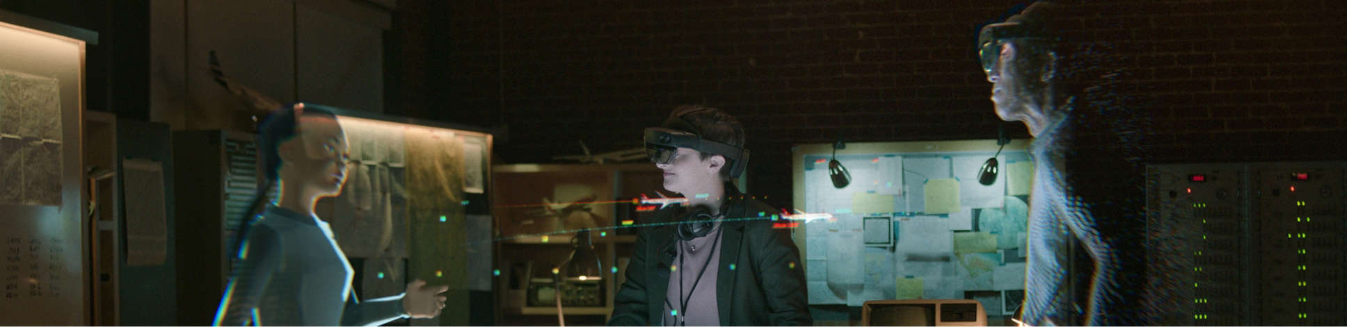 Three people wearing HoloLens 2 having a meeting in augmented reality.