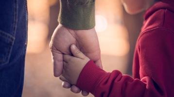 ילד ואדם מבוגר מחזיקים ידיים.