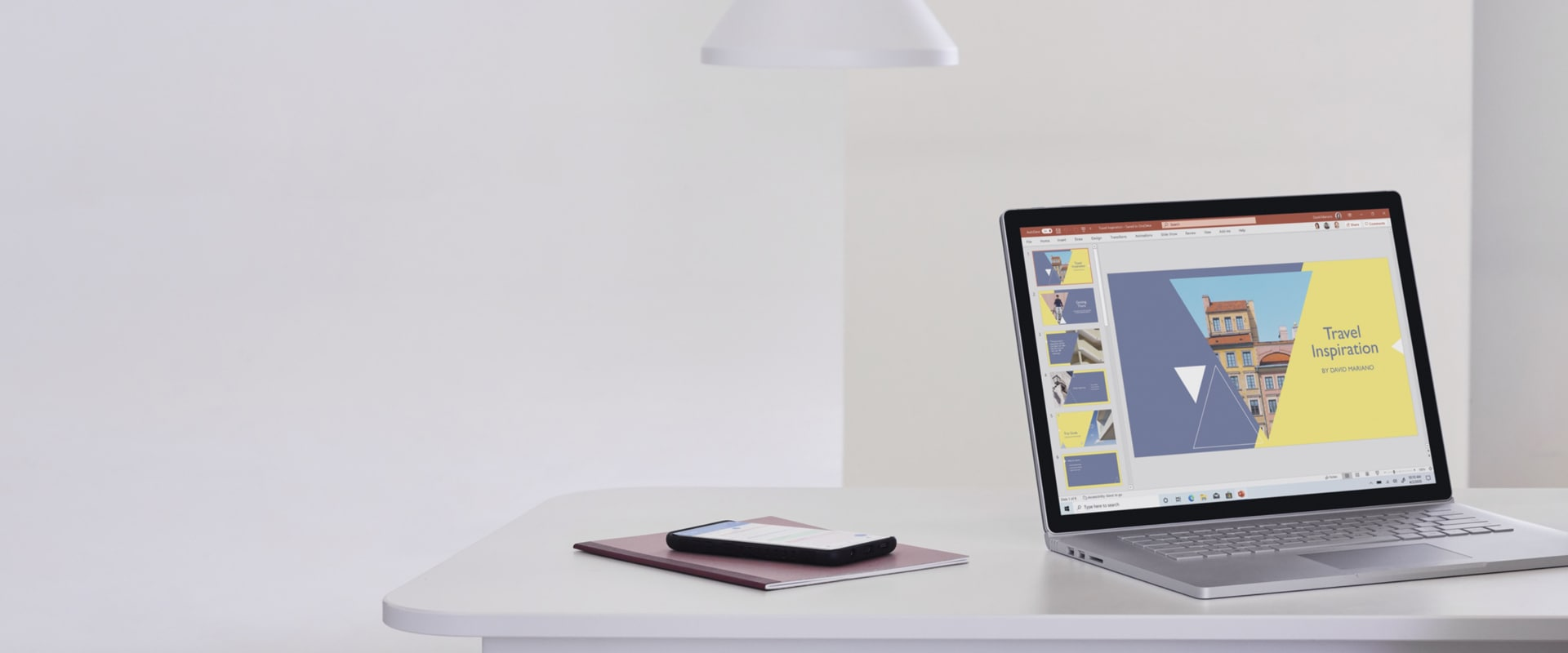 A laptop sits on a desk next to a notebook and phone. A PowerPoint file open on the laptop screen