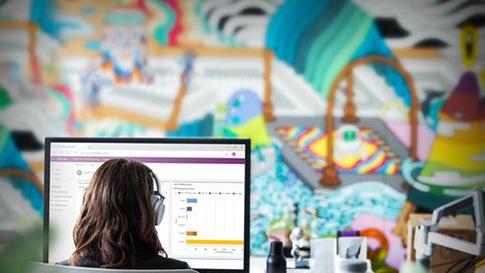 Eine Frau sitzt vor einem Computerbildschirm. Auf dem Bildschirm sieht mein ein Balkendiagramm eines Power Platform Tools.