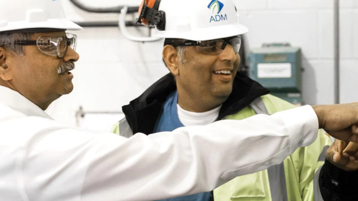 Workers wearing hard hats having a conversation