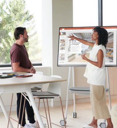 A person giving a PowerPoint presentation to a colleague in an open office.