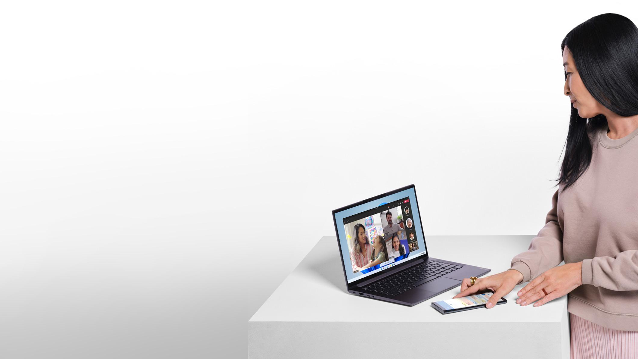 Femme avec un téléphone qui regarde un ordinateur portable avec écran Windows11