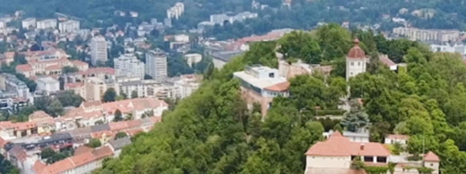 Bild zeigt eine Stadt von oben, auf dem ein Hügel voll mit Bäumen im Fokus steht.
