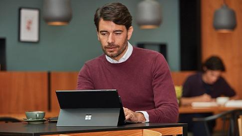 Ein Mann in einem dunkelroten Pullover sitzt in einem Café vor seinem Microsoft Surface Pro.