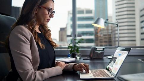Das Bild zeigt eine Frau am Laptop. Im Hintergrund sieht man durch ein Fenster einige Hochhäuser.