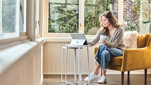 Eine Frau sitzt mit einem Kaffee in der Hand in einem orangenen Sessel. Auf dem Tisch vor ihr befindet sich ein Microsoft Surface Pro.