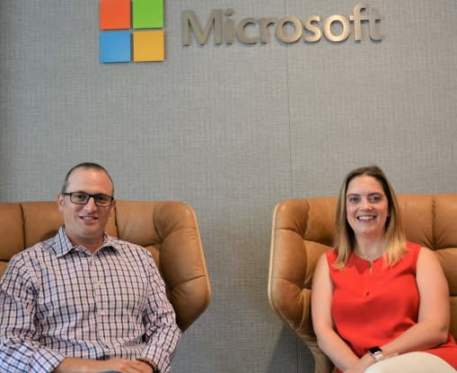 Danielle Yedinak and David Laves sit and smile below a Microsoft logo inside a Microsoft building.
