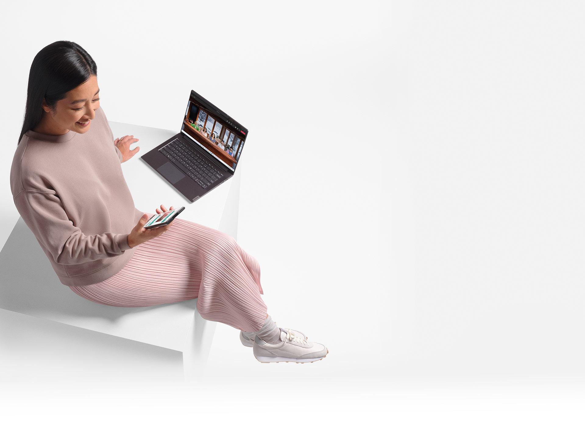 Bilgisayarın yanında oturan kadın telefonuna bakarak gülümsüyor
