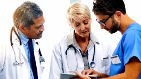 Drei Ärzte stehen nebeneinander. Einer zeigt den beiden anderen etwas am Tablet.