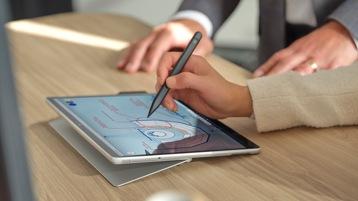 Surface ペンを使って Surface Pro 8 for Business の画面に何かを書いている人物の手。