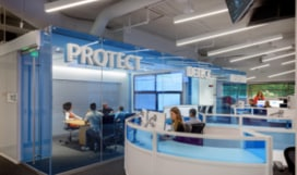 An office full of people working at desks and in conference rooms and the words Protect and Detect hung on the walls.