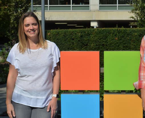 Danielle Yedinak and David Laves stand and smile on either side of a Microsoft logo outside a Microsoft building.