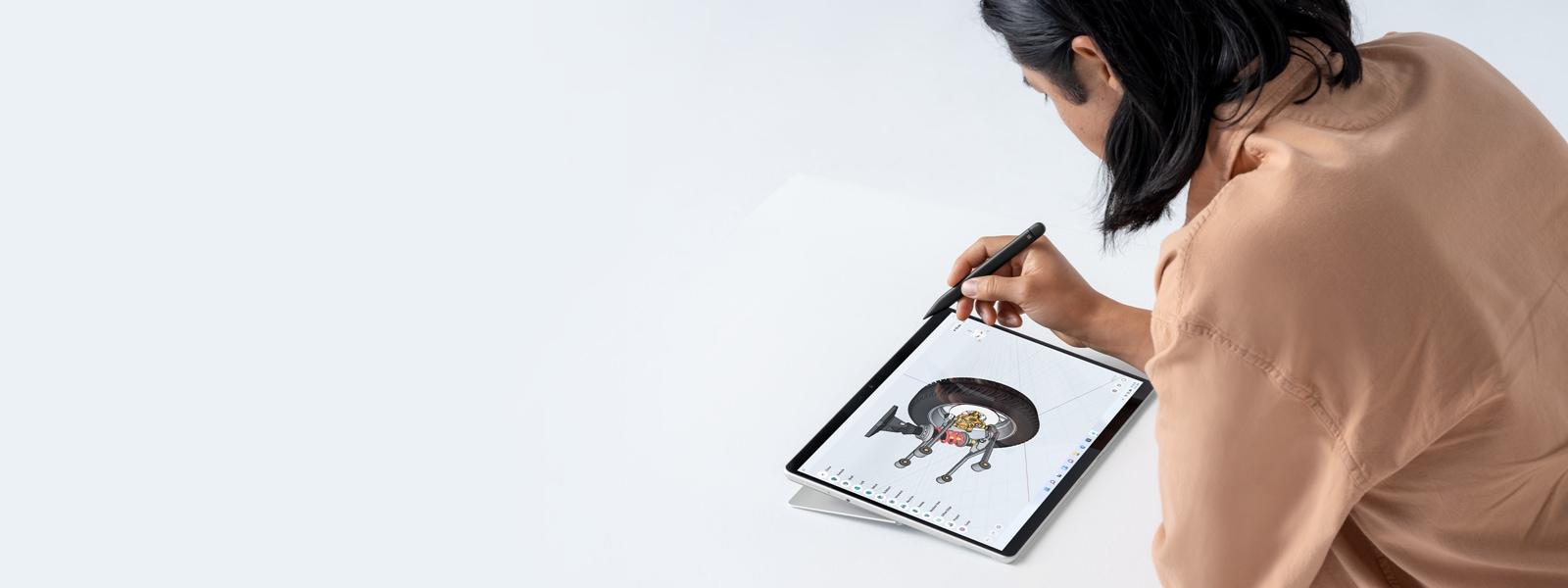 คนคนหนึ่งกำลังถือปากกา Surface และทำงานด้วย Surface Pro 8
