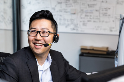 A customer service representative wearing a headset and smiling.