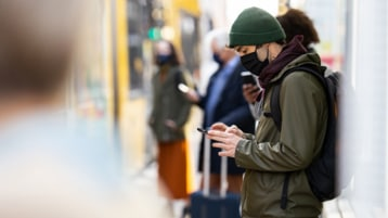 A person wearing PPE looking at a mobile phone while waiting for public transportation.