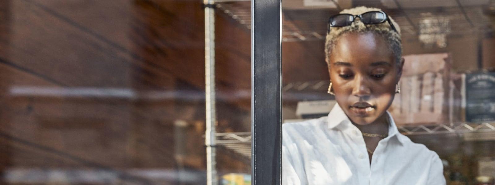 Γυναίκα στέκεται πίσω από ένα παράθυρο και εργάζεται στον φορητό υπολογιστή της