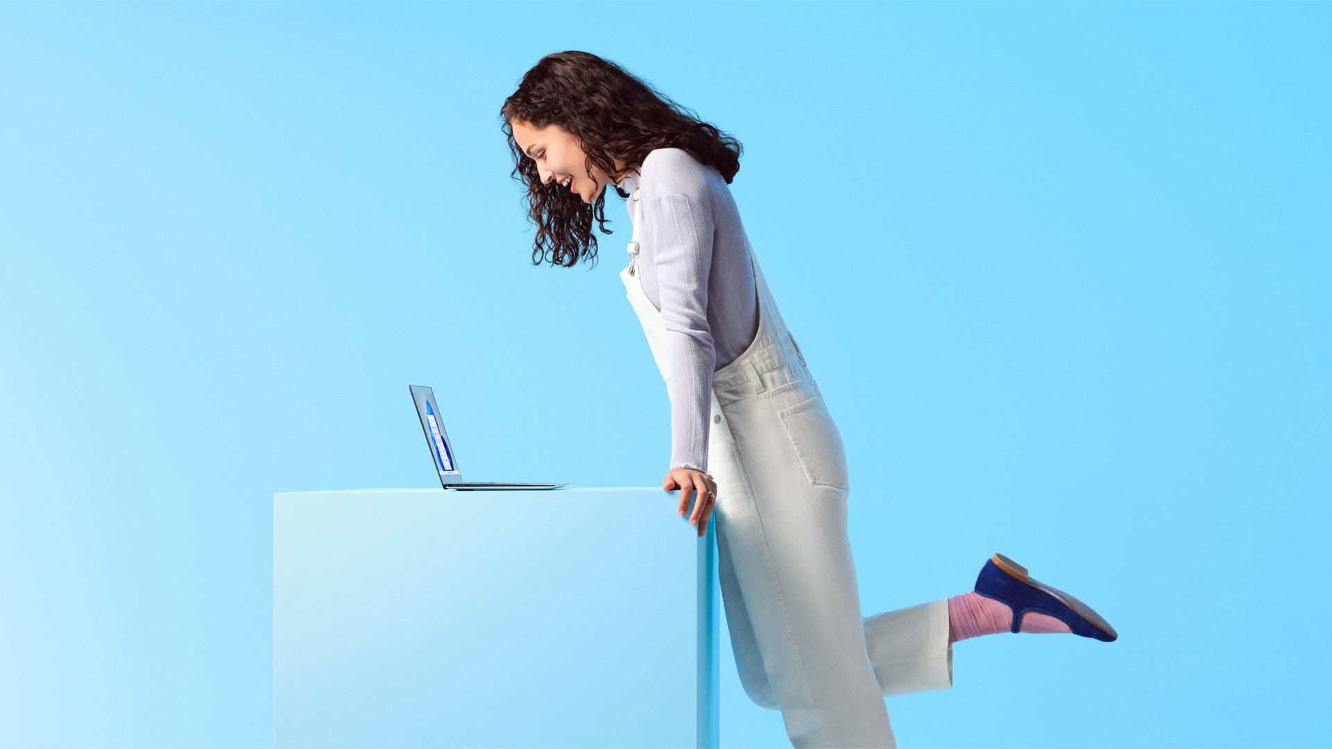Femme souriante regardant un ordinateur portable