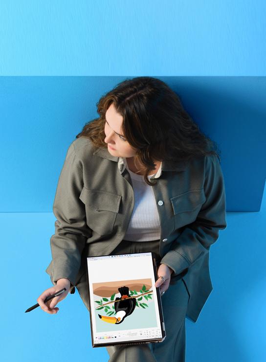 Femme avec un appareil sur ses genoux utilisant un stylo numérique