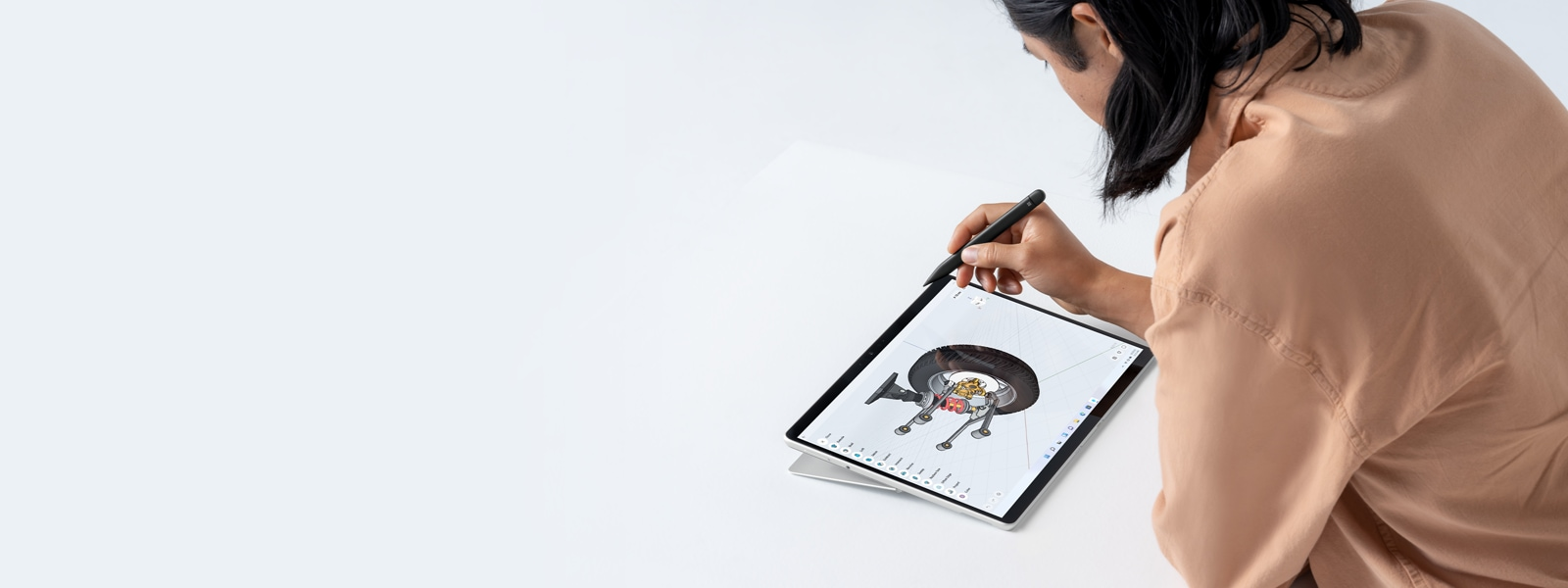 A person holding a Surface Pen working with Surface Pro 8.